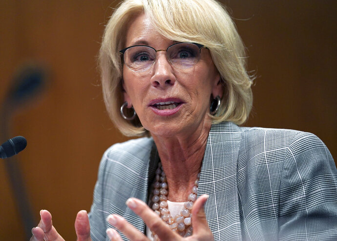 """FILE - In this June 5, 2018, file photo, Education Secretary Betsy DeVos testifies during hearing on the FY19 budget on Capitol Hill in Washington. A federal court has ruled that a decision by DeVos to delay an Obama-era rule meant to protect students swindled by for-profit colleges was """"arbitrary and capricious,"""" dealing a significant blow to the Trump administration's attempt to ease regulations for the industry.   (AP Photo/Carolyn Kaster, File)"""