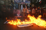 Pakistani Shiite Muslims burn representations of Israeli flags during a rally to protest the move of the U.S. embassy from Tel Aviv to Jerusalem, in Karachi, Pakistan, Wednesday, May 16, 2018. (AP Photo/Fareed Khan)