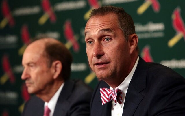 FILE - In this June 30, 2017, file photo, John Mozeliak, right, newly named St. Louis Cardinals president of baseball operations, speaks during a news conference at Busch Stadium in St. Louis. St. Louis' series opener against the Chicago White Sox has been postponed to Saturday, Aug. 15, 2020, giving the Cardinals an extra day to recover from a coronavirus outbreak. The Cardinals, who have not played since July 29, were set to resume their season Friday night in Chicago. But the series opener was pushed back to a doubleheader on Saturday, the beginning of an extended stay in the Windy City for the Cards. (Robert Cohen/St. Louis Post-Dispatch via AP, File)