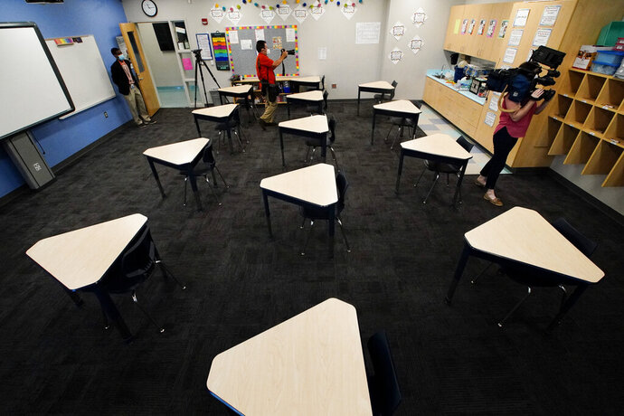 Media members document the inside of a fifth grade classroom set up for social distancing during a media demonstration at A.J. Whittenberg Elementary School of Engineering Monday, July 20, 2020, in Greenville, S.C. (AP Photo/Chris Carlson)