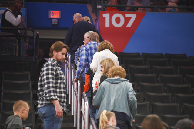 Basketball fans leave Chesapeake Energy Arena after it is announced that an NBA basketball game between Oklahoma City Thunder and Utah Jazz in Oklahoma City has been postponed, Wednesday, March 11, 2020. (AP Photo/Kyle Phillips)