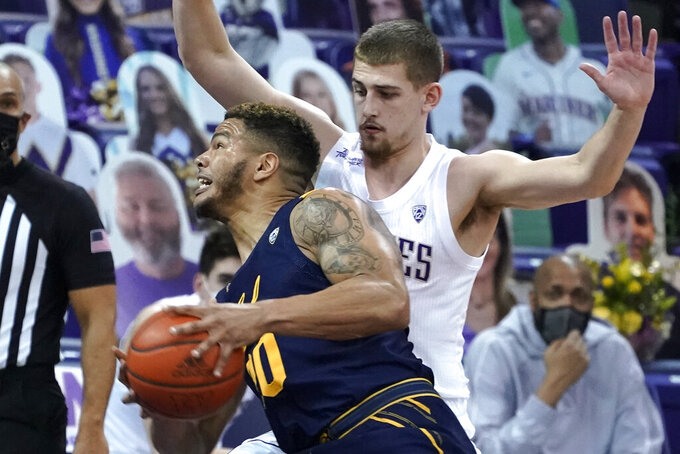 California guard Matt Bradley, left, drives around Washington guard Erik Stevenson, right, during the first half of an NCAA college basketball game, Saturday, Feb. 20, 2021, in Seattle. (AP Photo/Ted S. Warren)