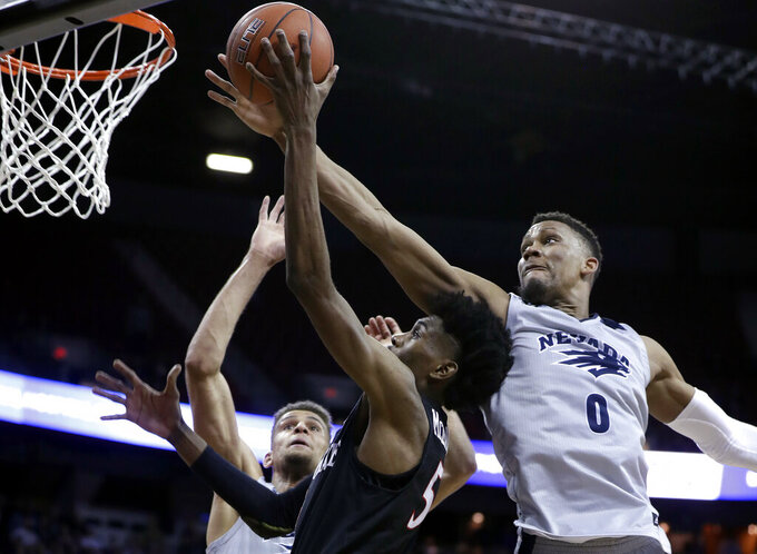 Nevada's Tre'Shawn Thurman (0) attempts to block a shot from San Diego State's Jalen McDaniels (5) during the second half of an NCAA college basketball game in the Mountain West Conference men's tournament Friday, March 15, 2019, in Las Vegas. (AP Photo/Isaac Brekken)