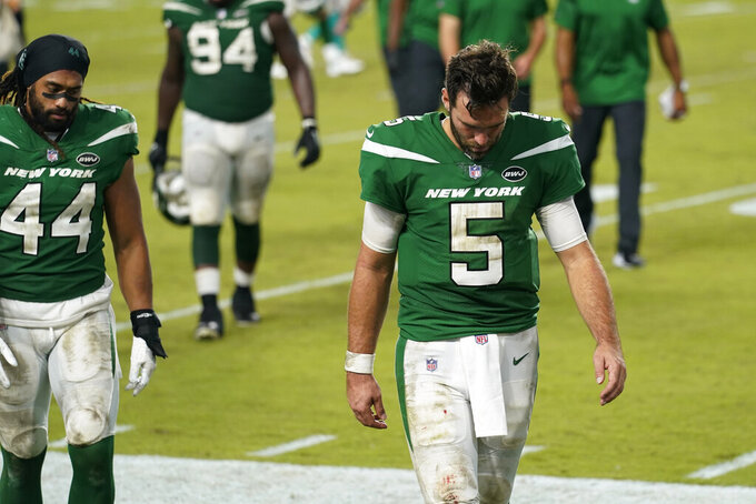 New York Jets quarterback Joe Flacco (5) and linebacker Harvey Langi (44) walk off the field during the end of an NFL football game against the Miami Dolphins, Sunday, Oct. 18, 2020, in Miami Gardens, Fla. The Dolphins defeated the Jets 24-0. (AP Photo/Lynne Sladky)