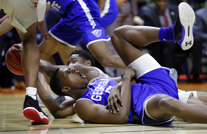 Georgia State's Jordan Tyson, front, yells out in pain after scrambling for a loose ball with Houston's Brison Gresham, rear, during the second half of a first round men's college basketball game in the NCAA Tournament Friday, March 22, 2019, in Tulsa, Okla. (AP Photo/Jeff Roberson)