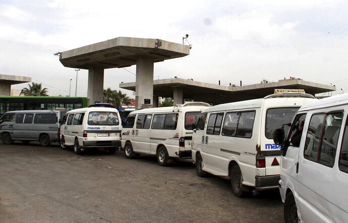 FILE - In this file photo released on April 7, 2019, by the Syrian official news agency SANA, shows vans queuing to fill their tanks with fuel, at a gas station in Daraa, south Syria.  On Sunday, Jan. 10, 2021, Syria's petroleum ministry blamed U.S. sanctions for forcing it to cut by up to 24% its distribution of fuel and diesel because of delays in arrival of needed supplies. (SANA via AP, File)