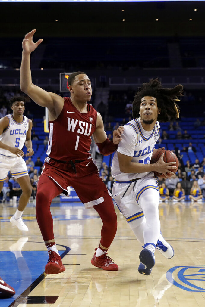 UCLA guard Tyger Campbell, right, is defended by Washington State guard Jervae Robinson (1) during the first half of an NCAA college basketball game Thursday, Feb. 13, 2020, in Los Angeles. (AP Photo/Marcio Jose Sanchez)