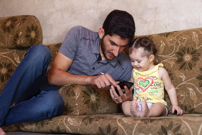 """In this Sunday September 1, 2019 photo, Syrian Abdel Hamid al-Yousef, plays with his 11-month-old daughter Aya, at a displaced settlement near the Turkish border called """"Mokhayyam al-Karamah,"""" Arabic for """"Dignity Camp,"""" near the town of Atmeh, in northern Syria. Al-Yousef lost his baby twins, his wife and 16 other relatives in the poison gas attack that hit Syria's Khan Sheikhoun in April 2017. Determined to continue with his life, he remarried, and has an 11-month-old daughter. But tragedy keeps chasing the 31-year-old former shopkeeper as he recently fled a government assault on Idlib and the nonstop bombardment of Khan Sheikhoun. (AP Photo)"""