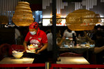 An employee wearing a face mask to protect against the coronavirus clears a table at a restaurant in a shopping mall in Beijing, Friday, Aug. 14, 2020. China's factory output rose just under 5% last month from a year earlier while retail sales fell slightly, suggesting the country's recovery from the coronavirus pandemic remains muted. (AP Photo/Mark Schiefelbein)