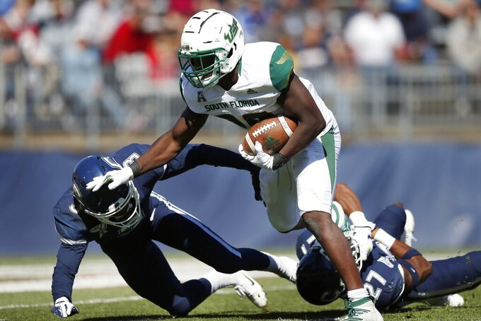 South Florida running back Trevon Sands (28) carries for a touchdown against Connecticut defensive back Diamond Harrell, left, and linebacker Omar Fortt (27) during the first half of an NCAA college football game in East Hartford, Conn., Saturday, Oct. 5, 2019. (AP Photo/Michael Dwyer)
