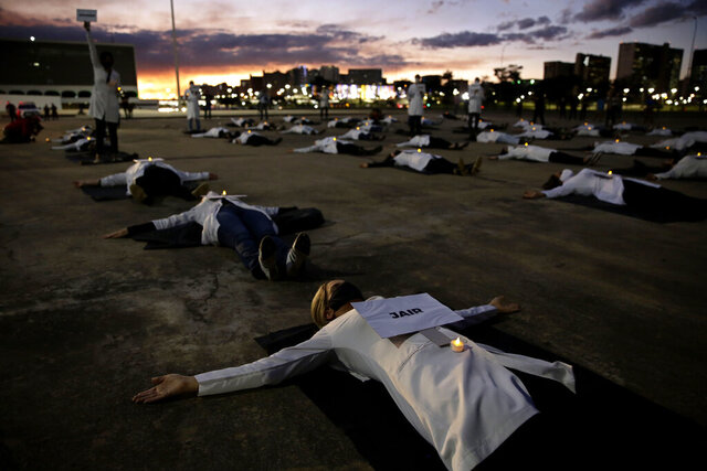 Nurses lay on the ground to represent colleagues who died in their fight against the new coronavirus pandemic, during a protest marking International Nurses Day, in Brasilia, Brazil, Tuesday, May 12, 2020. (AP Photo/Eraldo Peres)