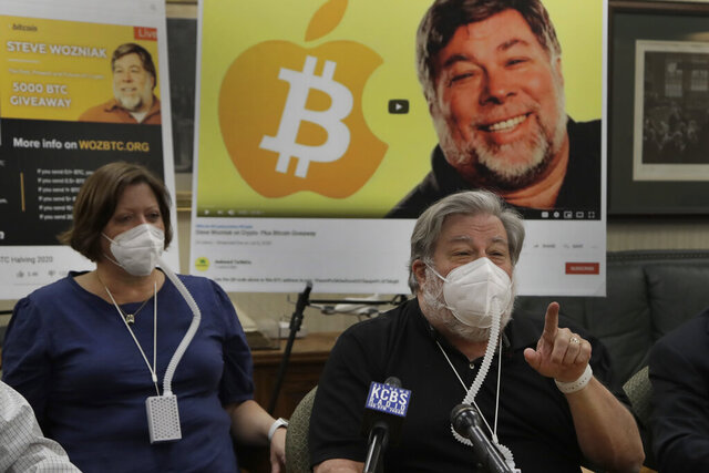 Apple co-founder Steve Wozniak, right, gestures beside his wife Janet Hill during a media conference on Thursday, July 23, 2020, in Burlingame, Calif. Wozniak is launching a legal attack against Google's YouTube video site for allowing con artists to use him as a pawn in a Bitcoin scam believed to have heisted millions of dollars from people around the world. (AP Photo/Ben Margot)