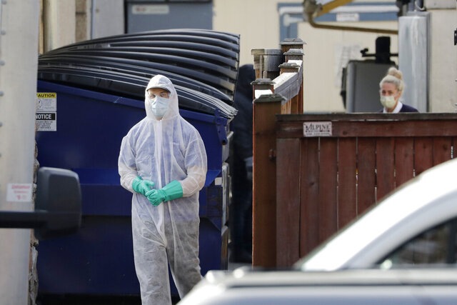 A member of a cleaning crew heads toward a vehicle after working at the Life Care Center, where at least 30 coronavirus deaths have been linked to the facility, Wednesday, March 18, 2020, in Kirkland, Wash. Staff members who worked while sick at multiple long-term care facilities contributed to the spread of COVID-19 among vulnerable elderly in the Seattle area, federal health officials said Wednesday. (AP Photo/Elaine Thompson)