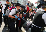Police arrest protestors at Oxford Circus in London, Friday, April 19, 2019. The environmental pressure group Extinction Rebellion is calling for a week of civil disobedience against what it says is the failure to tackle the causes of climate change. (AP Photo/Frank Augstein)