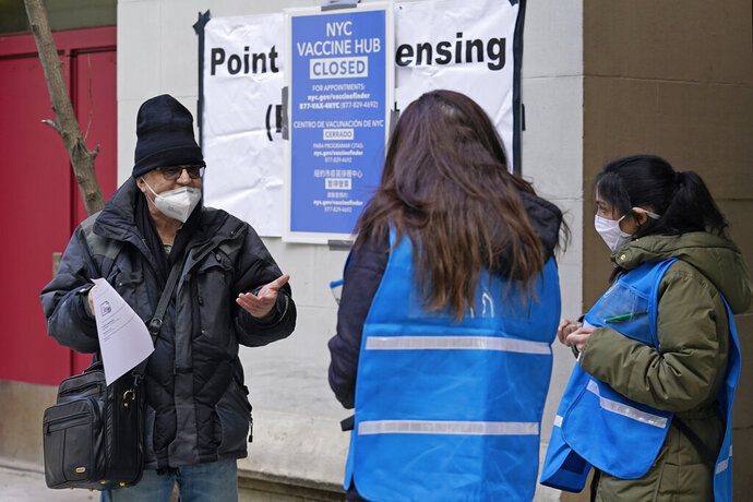 A man who came to get a COVID-19 vaccine holds his paperwork as he talks to a New York City health department worker outside a closed vaccine hub, Thursday, Jan. 21, 2021, in the Brooklyn borough of New York. Public health experts are blaming COVID-19 vaccine shortages around the U.S. in part on the Trump administration's push to get states to vastly expand their vaccination drives to reach the nation's estimated 54 million people age 65 and over. The push that began over a week ago has not been accompanied by enough doses to meet demand, leading to frustration and confusion. (AP Photo/Kathy Willens)