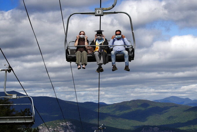 Kennett High School graduate Cole Bradley and his parents adjust their masks while riding on a ski chairlift to the summit of Cranmore Mountain Resort to receive his diploma, Saturday, June 13, 2020, in North Conway, N.H. The school came up with a unique commencement ceremony in order to adhere to the social-distancing guidelines necessitated by the coronavirus pandemic. Bradley, who was a senior class representative, is attending Indiana University in the fall. (AP Photo/Robert F. Bukaty)