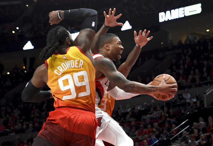 Portland Trail Blazers guard Damian Lillard, right, drives to the basket past Utah Jazz forward Jae Crowder, front, during the second half of an NBA basketball game in Portland, Ore., Wednesday, Jan. 30, 2019. (AP Photo/Steve Dykes)