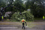 Des Moines city crews remove a tree fallen on Hickman Road, on Monday, Aug. 10, 2020, in Des Moines, Iowa after a storm with gusts more than 80 mph blew through the city. (Kelsey Kremer/The Des Moines Register via AP)