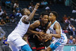 Miami Heat forward KZ Okpala, center, fights through a double-team by Charlotte Hornets forwards Michael Kidd-Gilchrist, left, and PJ Washington during the second half of an NBA preseason basketball game in Charlotte, N.C., Wednesday, Oct. 9, 2019. (AP Photo/Nell Redmond)