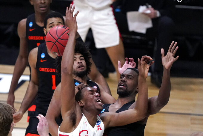 Houston forward Fabian White Jr. loses the ball while driving to the basket in front of Oregon State forward Dearon Tucker, right, during the first half of an Elite 8 game in the NCAA men's college basketball tournament at Lucas Oil Stadium, Monday, March 29, 2021, in Indianapolis. (AP Photo/Michael Conroy)