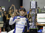 FILE - In this May 18, 2019, file photo, Kyle Larson poses with the trophy after winning the NASCAR All-Star Race at Charlotte Motor Speedway in Concord, N.C. Larson will be back in NASCAR next season driving the flagship No. 5 Chevrolet for Hendrick Motorsports after signing a multi-year contract Wednesday morning, Oct. 28, 2020, with Hendrick that ended his seven-month banishment from NASCAR for using a racial slur while playing an online racing game. (AP Photo/Chuck Burton, File)