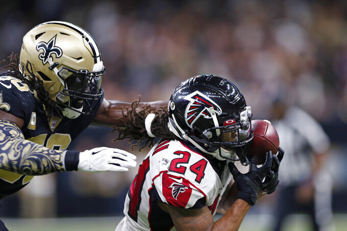 Atlanta Falcons running back Devonta Freeman (24) pulls in a pass in front of New Orleans Saints outside linebacker Demario Davis (56) in the first half of an NFL football game in New Orleans, Sunday, Nov. 10, 2019. (AP Photo/Rusty Costanza)