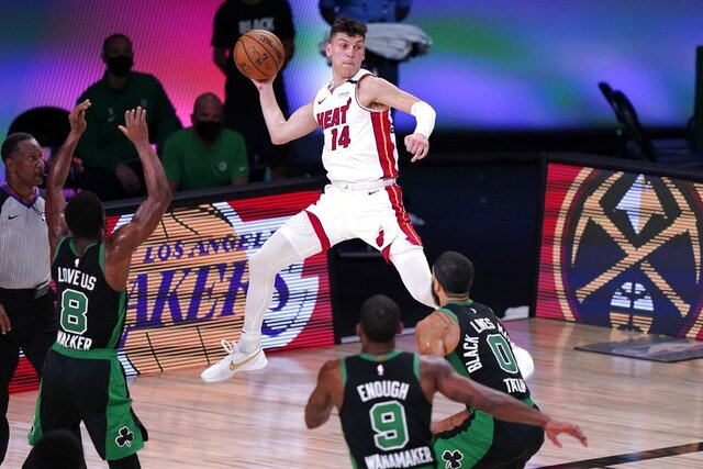 Miami Heat guard Tyler Herro (14) leaps to make a pass over Boston Celtics' Kemba Walker (8), Brad Wanamaker (9) and Jayson Tatum (0) during the second half of an NBA conference final playoff basketball game, Thursday, Sept. 17, 2020, in Lake Buena Vista, Fla. (AP Photo/Mark J. Terrill)