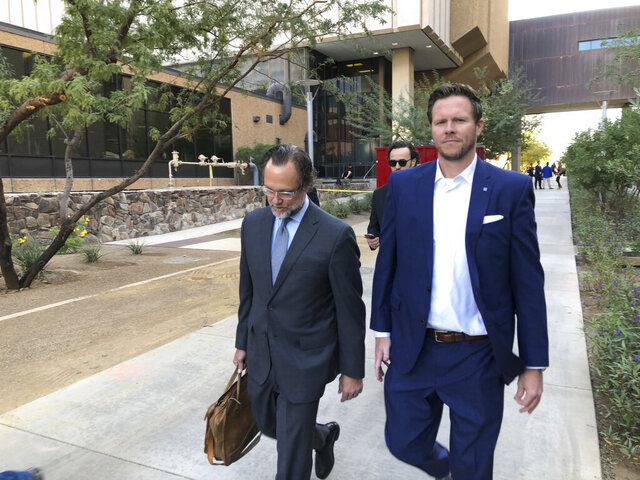 FILE - In this Nov. 5, 2019 file photo, former Maricopa County Assessor Paul Petersen, right, with his attorney, Kurt Altman, leave after a court hearing in Phoenix. Petersen, who admitted running an illegal adoption scheme in three states involving women from the Marshall Islands, was sentenced in Arkansas to six years in federal prison on Tuesday, Dec. 1, 2020. It was the first of three punishments he'll face for arranging adoptions prohibited by an international compact. (AP Photo/Jacques Billeaud, File)