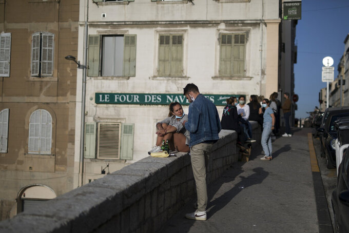 """Residents gather for drinks outdoors before curfew in Marseille, southern France, Friday, April 2, 2021. With France now Europe's latest virus danger zone, Macron on Wednesday ordered temporary school closures nationwide and new travel restrictions. But he resisted calls for a strict lockdown, instead sticking to his """"third way"""" strategy that seeks a route between freedom and confinement to keep both infections and a restless populace under control until mass vaccinations take over. (AP Photo/Daniel Cole)"""