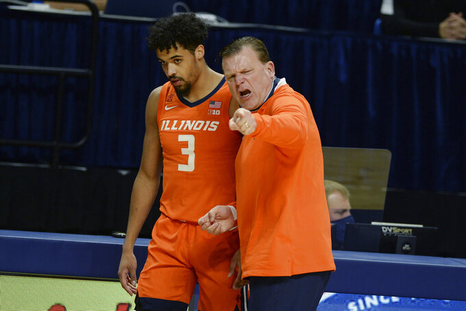 Illinois coach Brad Underwood talks to Jacob Grandison during the first half of the team's NCAA college basketball game against Penn State on Wednesday, Dec 23, 2020, in State College, Pa. (AP Photo/Gary M. Baranec)