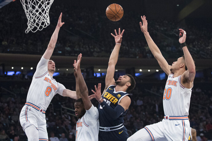 Denver Nuggets guard Jamal Murray,second from right, goes to the basket against New York Knicks forward Mario Hezonja (8), guard Emmanuel Mudiay (1) and forward Kevin Knox (20) during the first half of an NBA basketball game, Friday, March 22, 2019, at Madison Square Garden in New York. (AP Photo/Mary Altaffer)