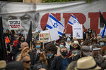 Protesters against Israel's Prime Minister Benjamin Netanyahu wave flags and banners outside his residence in Jerusalem, Sunday, May 24, 2020. Hundreds of protesters calling him the