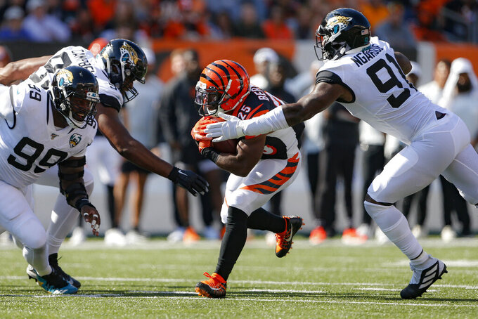 Cincinnati Bengals running back Giovani Bernard (25) runs the ball against Jacksonville Jaguars defensive end Yannick Ngakoue (91) in the first half of an NFL football game, Sunday, Oct. 20, 2019, in Cincinnati. (AP Photo/Gary Landers)