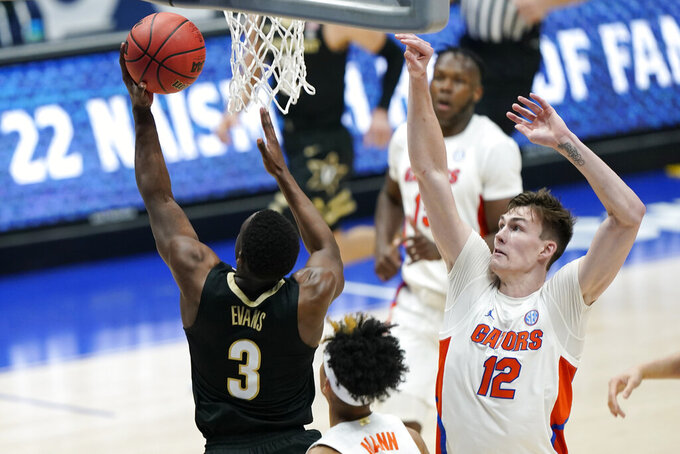 Vanderbilt's Maxwell Evans (3) shoots against Florida's Colin Castleton (12) in the second half of an NCAA college basketball game in the Southeastern Conference Tournament Thursday, March 11, 2021, in Nashville, Tenn. (AP Photo/Mark Humphrey)