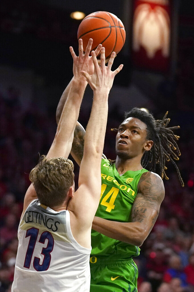 Oregon forward C.J. Walker (14) shoots over Arizona forward Stone Gettings during the first half of an NCAA college basketball game Saturday, Feb. 22, 2020, in Tucson, Ariz. (AP Photo/Rick Scuteri)