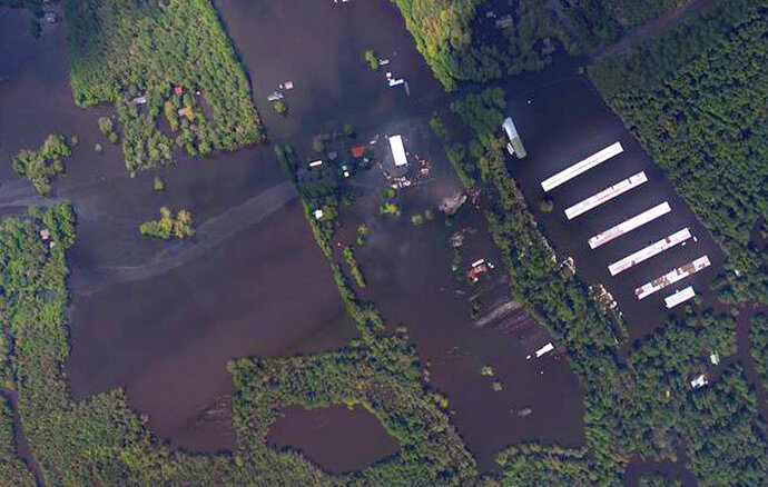 In this aerial photo taken Sept. 18, 2018 and released by the National Oceanic and Atmospheric Administration, an industrial site and a chicken farm outside Wallace, N.C., is seen that has been flooded by the nearby Northeast Cape Fear River following drenching rains from Hurricane Florence. (NOAA via AP)