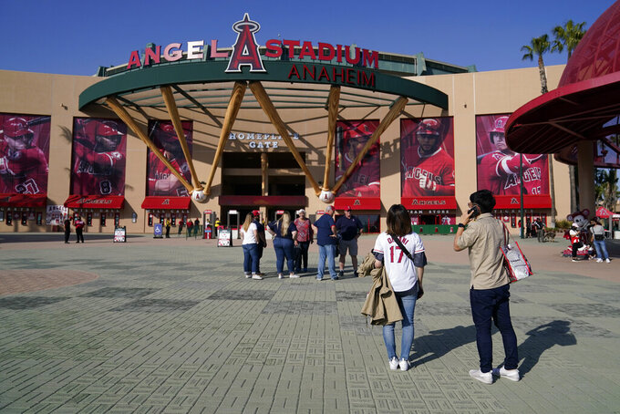 Fans stand outside Angel Stadium when a baseball game between the Minnesota Twins and the Los Angeles Angels was postponed Saturday, April 17, 2021, in Anaheim, Calif. MLB said the game was postponed to allow for continued COVID-19 testing and contact tracing involving members of the Twins organization. (AP Photo/Ashley Landis)