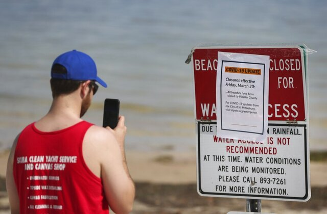 Zac Giparas, 28, takes a picture of the Covid-19 update beach closure sign along the sand at North Shore Park on Friday, March 20, 2020 in St. Petersburg. Giparas is a USF grad student currently on spring break. (Dirk Shadd/Tampa Bay Times via AP)