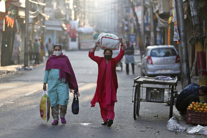 Indian women wearing face masks as a precaution against the coronavirus walk through a street in the morning in Jammu, India, Wednesday, Nov.18, 2020. (AP Photo/Channi Anand)