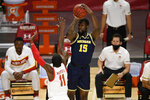 Michigan guard Chaundee Brown (15) shoots next to Maryland guard Darryl Morsell (11) during the first half of an NCAA college basketball game Thursday, Dec. 31, 2020, in College Park, Md. (AP Photo/Nick Wass)