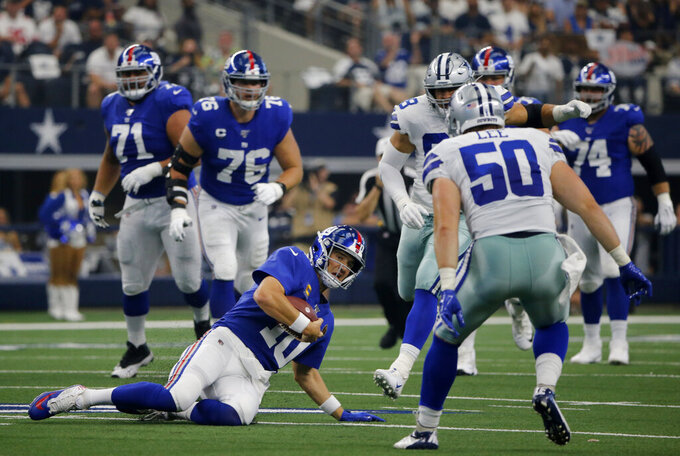New York Giants quarterback Eli Manning (10) comes to a sliding stop after a short gain as Dallas Cowboys outside linebacker Sean Lee (50) closes in in the first half of a NFL football game in Arlington, Texas, Sunday, Sept. 8, 2019. (AP Photo/Michael Ainsworth)