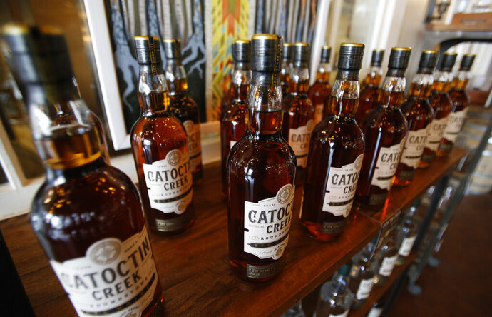 FILE - In this June 20, 2018 file photo, Catoctin Creek Distillery whiskey is on display in a tasting room in Purcellville, Va. American whiskey producers feeling the pain from the Trump administration's trade disputes have gotten a shot of relief with an agreement announced Friday, May 24, 2019 that will end retaliatory tariffs that Canada and Mexico slapped on whiskey and other U.S. products. (AP Photo/Steve Helber, File)