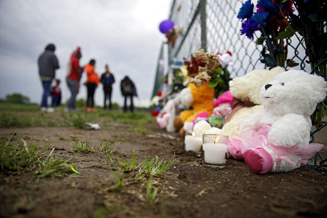 In this Wednesday, May 27, 2020 photo, mourners grieve at a makeshift memorial at the spot where Miracle Crook, 3, and Tony Crook, 2, walked down to Mingo Creek at the Shoreline Apartments in Tulsa. Okla. Police said Wednesday a body found in an east Tulsa creek is believed to be that of a second missing toddler who disappeared with his sister last week.  (Mike Simons/Tulsa World via AP)