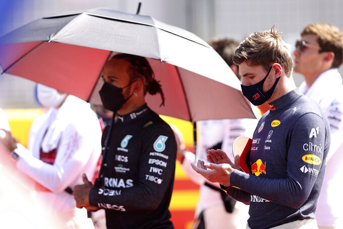 Red Bull driver Max Verstappen of the Netherlands and Mercedes driver Lewis Hamilton of Britain, left, stand on the grid before the start of the British Formula One Grand Prix, at the Silverstone circuit, in Silverstone, England, Sunday, July 18, 2021. (Lars Baron/Pool photo via AP)