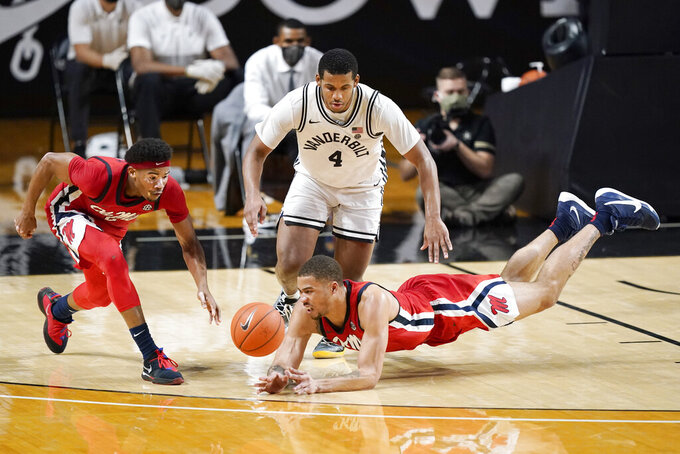 Mississippi's Devontae Shuler, left, and KJ Buffen, right, reach for a loose ball with Vanderbilt's Jordan Wright (4) in the first half of an NCAA college basketball game Saturday, Feb. 27, 2021, in Nashville, Tenn. (AP Photo/Mark Humphrey)