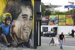 In this Nov. 7, 2019 photo, a mural depicts legendary Brazilian F1 driver Ayrton Senna on a business front near the Interlagos racetrack in Sao Paulo, Brazil. Many bars on busy streets like Avenida Paulista are open 24 hours a day during the Brazil F1 GP race, and hotels prepare feasts at early hours so fans don't need to refuel at the track. (AP Photo/Nelson Antoine)
