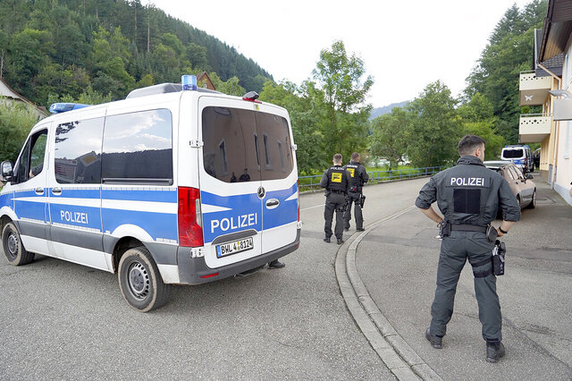 Police officers stand in front of a driveway in a forest area near Oppenau, Germany, Friday, July 17, 2020. A man who disarmed four officers at gunpoint in southwestern Germany before fleeing into the Black Forest has been arrested after a five-day manhunt. Police, including special forces and a sniffer dog, moved in after two witnesses reported seeing a man who fitted the profile of suspect Yves Rausch on Friday afternoon. (Benedikt Spether/dpa via AP)