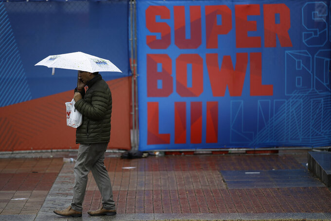 A person walks through Centennial Olympic Park on a rainy morning ahead of the NFL Super Bowl 53 football game, Tuesday, Jan. 29, 2019, in Atlanta. The New England Patriots face the Los Angeles Rams Sunday, Feb., 2, 2019. (AP Photo/Matt Rourke)