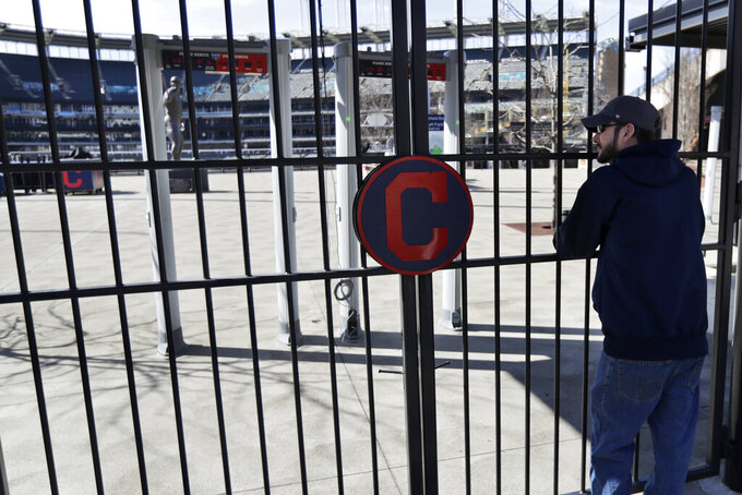 FILE - In this March 26, 2020, file photo, Jason Hackedorn looks into Progressive Field, home of the Cleveland Indians baseball team, in Cleveland. With the distinct possibility of pro sports resuming in empty venues, a recent poll suggests a majority of U.S. fans wouldn't feel safe attending games anyway without a coronavirus vaccine.(AP Photo/Tony Dejak, File)