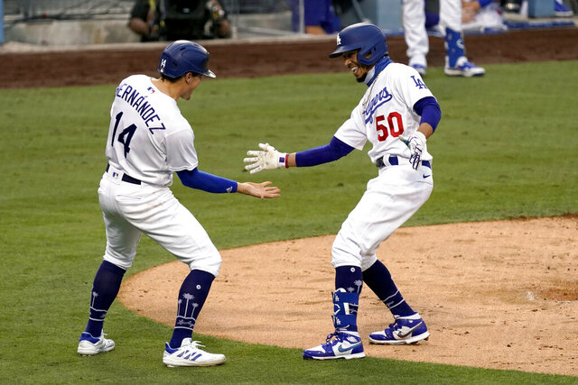 Los Angeles Dodgers' Mookie Betts, right, gets congratulations from Enrique Hernandez, after Betts hits a two-run home run against the Houston Astros during the fifth inning of a baseball game in Los Angeles, Sunday, Sept. 13, 2020. (AP Photo/Alex Gallardo)